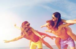 Le vänner som har gyckel på sommarstranden Arkivfoto