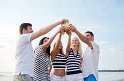 Le vänner som klirrar flaskor på stranden Arkivbilder
