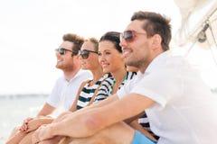Le vänner som sitter på yachtdäck Arkivbild