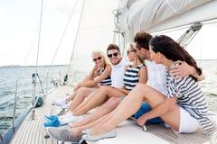 Le vänner som sitter på yachtdäck fotografering för bildbyråer