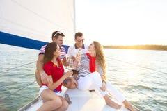 Le vänner som sitter på yachtdäck och hälsar dricka chamen arkivfoto