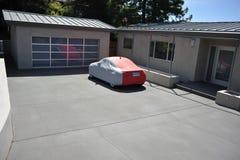 Le véhicule couvert se repose dans l'allée de la maison moderne Images stock
