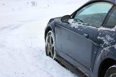 Le véhicule d'Unrecognizeable a collé dans le champ de neige photographie stock