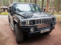 Le véhicule noir de Hummer H2 se tient sur la route de campagne sale Images stock
