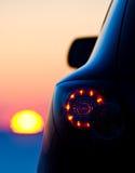 Le véhicule a stationné devant le coucher du soleil Photos libres de droits