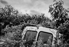 Le véhicule utilitaire abandonné vu a collé dans une bordure de haies Photo libre de droits