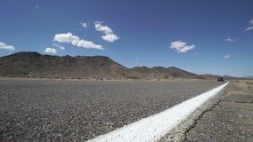 Le véhicule voyage le long d'une route dans le désert