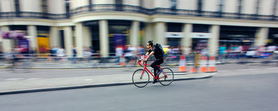 Le vélo d'équitation de cycliste jeûnent par la ville Tache floue de vitesse photos stock