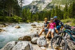 Le vélo de famille monte dans les montagnes tout en détendant sur le riverba photos libres de droits