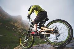 Le vélo de montagne extrême folâtre l'homme d'athlète dans le casque montant dehors sur un fond des roches lifestyle épreuve photo stock
