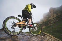 Le vélo de montagne extrême folâtre l'homme d'athlète dans le casque montant dehors sur un fond des roches lifestyle épreuve image stock