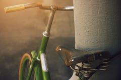 Le vélo de vert de cru avec une vieille selle est fixé dans le tuyau image stock