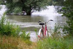 Le vélo rouge de dames se tiennent prêt le lac Photo libre de droits