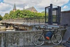 Le vélo se tient au pont contre le contexte d'une cathédrale catholique Kaliningrad, Kant Island photos stock