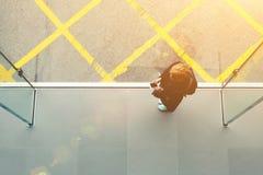 Le vagabond féminin blond lit des informations sur la ville sur la page Web par l'intermédiaire du téléphone de cellules Photographie stock libre de droits