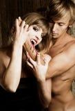 Le vampire féminin veut mordre un jeune homme photographie stock