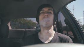 Le vaper d'homme fait la fumée avec la cigarette électronique se reposant dans la voiture dans au ralenti banque de vidéos