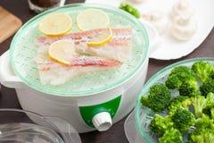 Le vapeur avec les poissons et le brocoli dans la cuisine Images stock