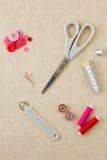 Accessori di cucito nei toni rossi e rosa fotografia stock libera da diritti