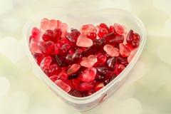 Le vase transparent à forme de coeur (cuvette) a rempli de gelées colorées de forme de coeur (de rouge), coeurs légers fond, fin  Photographie stock