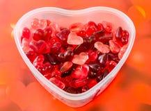 Le vase transparent à forme de coeur (cuvette) a rempli de gelées colorées de forme de coeur (de rouge), coeurs rouges fond, fin  Image libre de droits