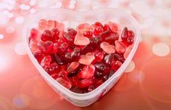 Le vase transparent à forme de coeur (cuvette) a rempli de gelées colorées de forme de coeur (de rouge), fond rouge de bokeh, fin Photographie stock
