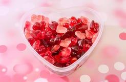 Le vase transparent à forme de coeur (cuvette) a rempli de gelées colorées de forme de coeur (de rouge), fond rouge de bokeh, fin Photos libres de droits
