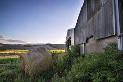 Le vecchie balle di fieno e del granaio nella campagna dell'estate abbelliscono Fotografia Stock