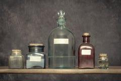 Le vecchie bottiglie di vetro sono in un laboratorio fotografie stock