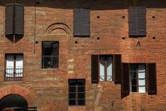 Le vecchie finestre con gli otturatori sul mattone rosso medievale hanno strutturato la parete, I Immagine Stock