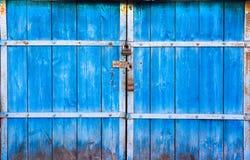 Le vecchie grandi porte di legno dipinte in blu ed in chiuso sul lucchetto Il portone blu sulla serratura Primo piano di legno de immagini stock