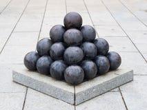 Le vecchie palle di cannone nere del ferro hanno sistemato nella forma della piramide Immagini Stock Libere da Diritti