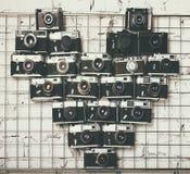 Le vecchie retro macchine fotografiche nel cuore amano la forma di fotografia Immagine Stock