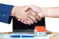 Le vendeur à la maison se serre la main, la maison de stylo et de modèle sur le plan de maison Photos stock