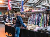 Le vendeur arrange des chapeaux à vendre sur le niveau supérieur du St de croix de Charing Image stock