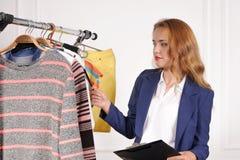 Le vendeur dans un magasin d'habillement recalcule des marchandises sur le cintre Image libre de droits