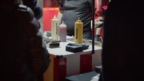 Le vendeur de camion de nourriture sert les hot-dogs la nuit banque de vidéos
