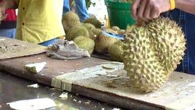 Le vendeur de fruit épluche le durian banque de vidéos