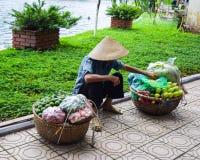 Le vendeur de fruit marche avec un poteau de transport dans le vieux quart Les 36 vieilles rues Image stock