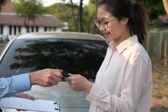 Le vendeur donnent la clé de voiture au client voiture de achat de femme de revendeur photographie stock