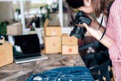 Le vendeur en ligne prennent une photo de produit pour le téléchargement à l'onli de site Web image libre de droits