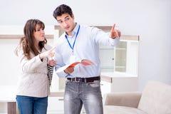 Le vendeur expliquant à la cliente de femme au magasin de meubles Photo stock