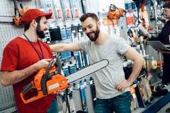 Le vendeur montre à client barbu la nouvelle tronçonneuse dans le magasin de machines-outils photo libre de droits