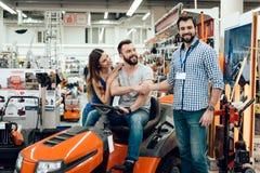 Le vendeur montre des couples de nouvelle machine de nettoyage de clients dans le magasin de machines-outils Deux hommes se serra image stock