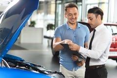 Le vendeur montre le moteur de voiture pour son client photographie stock