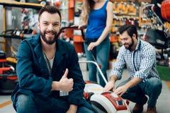Le vendeur pose avec des couples des clients et du nouveau moteur de pelouse dans le magasin de machines-outils photo libre de droits