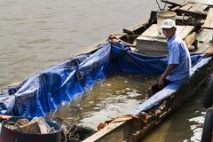 Le vendite del pescatore pescano sulla barca il 14 febbraio 2012 nel mio Tho, Vietnam V Fotografia Stock