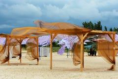 Le vent sur la plage secoue les rideaux en auvent pour une ombre photo libre de droits