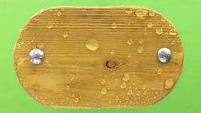 Le vent violent enlève à l'air comprimé des gouttes de l'eau avec le cadre ovale en bois D'isolement sur le fond vert banque de vidéos
