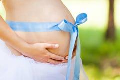Le ventre des femmes enceintes a attaché le ruban bleu Image stock